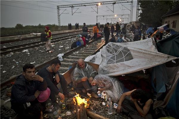 Một trẻ tị nạn Iraq nằm co ro trong lòng cha khi đám đông đốt lửa sưởi ấm ở ga tàu tại Tovarnik, Croatia. (Ảnh: AP)