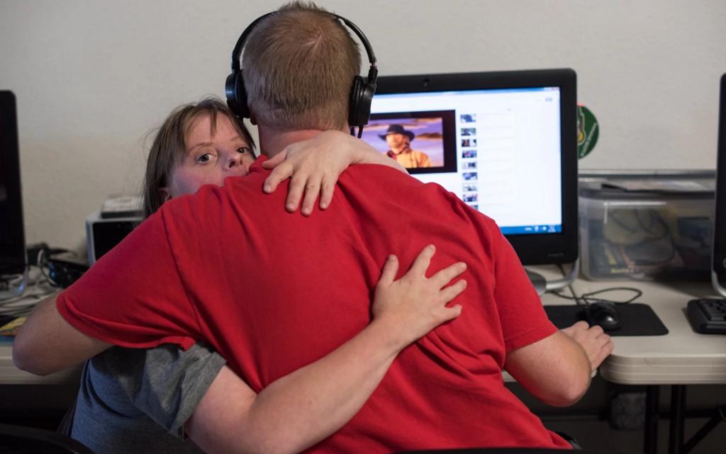 Hành động ấm áp của Krysta, ôm Nathaniel khi anh đang xem phim trên máy tính. Như biết bao cặp đôi khác, họ cũng muốn có không gian riêng để dành thời gian bên cạnh người yêu thương. (Ảnh: Internet)