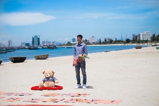 """Anh chàng đang đứng chờ bạn gái của mình với dòng chữ """"Làm bạn gái anh nhé"""" cũng như với một chú gấu bông và bó hoa trên tay."""