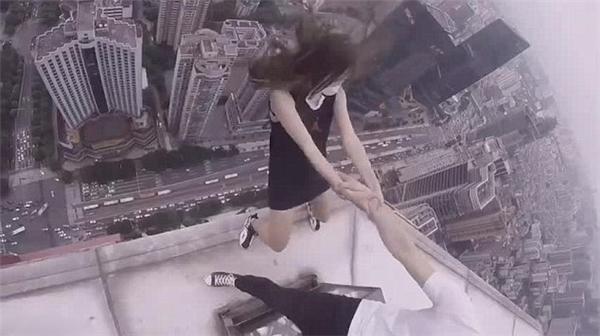 Cô gái nắm tay người đàn ông và thả một chân lơ lửng trên không.