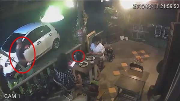 Tên thanh niên giả vờ nghe điện thoại và tiến gần tớibàn ăn nơi hai cô gái đang ngồi.(Ảnh: Cắt clip)