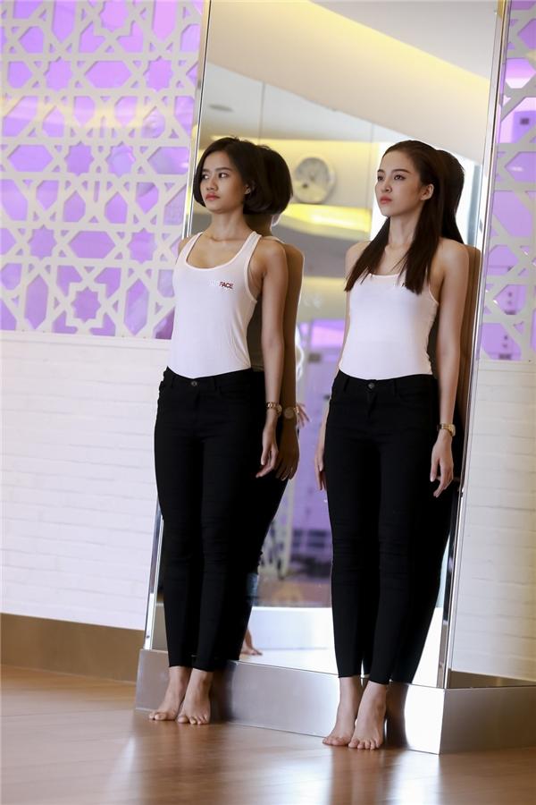 Thí sinh team Lan Khuê dựa người vào tườngđể tậpthẳng lưng khi catwalk.