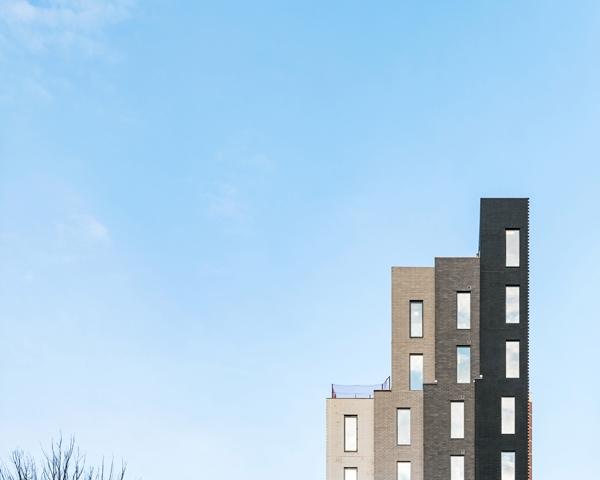 Tòa nhà có cấu trúc độc đáo với 4 tòa tháp mini lát gạch xám nhô cao, nổi bật trên nền trời với rất nhiều tòa nhà cao tầng khác vây quanh.