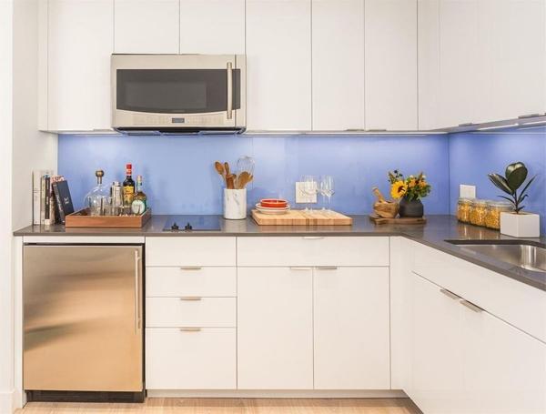 Bếp đầy đủ tiện nghi, các dụng cụ làm bếp được cất gọn gàng vào các hộc tủ bố trí bên dưới và trên tường bếp.