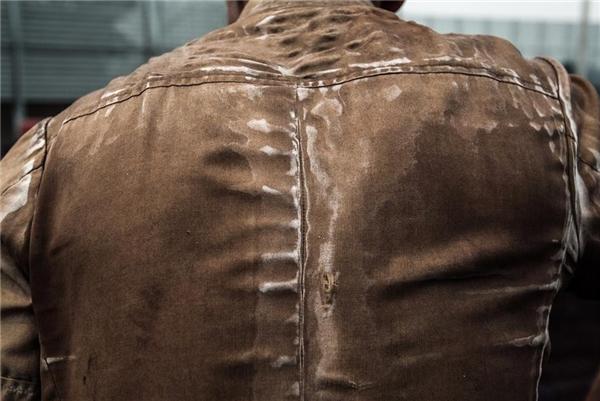Dấu vết mồ hôi lưu lại nơi chiếc áo chật chội bằng vải bố.
