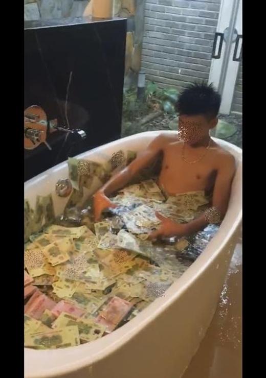 Chàng trai với thú vui tắm trong bồn nước đầy tiền. (Ảnh: Cắt clip)