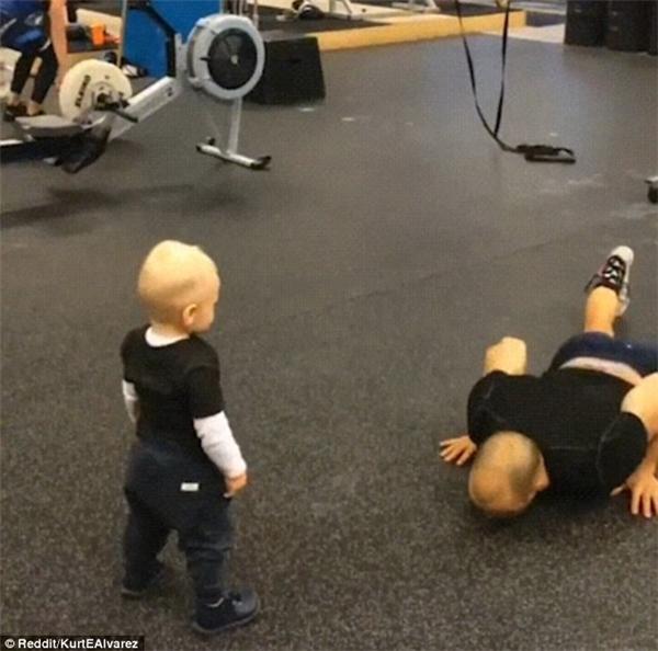 Cậu béchăm chú nhìn cha thực hành các động tác thể dục.