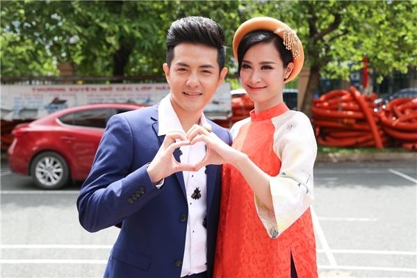 Đông Nhichọn áo dài cách tân của nhà thiết kế Thuỷ Nguyễn nền nã bên cạnh bạn traiÔng Cao Thắng.