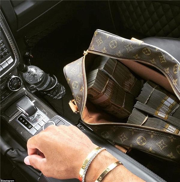 Danny Aghakhoe một chiếc túi hàng hiệu chứa đầy tiền mặt, cạnh đó là tay anh chàng đang mang một chiếc vòng tay đắt tiền.(Ảnh: Instagram)