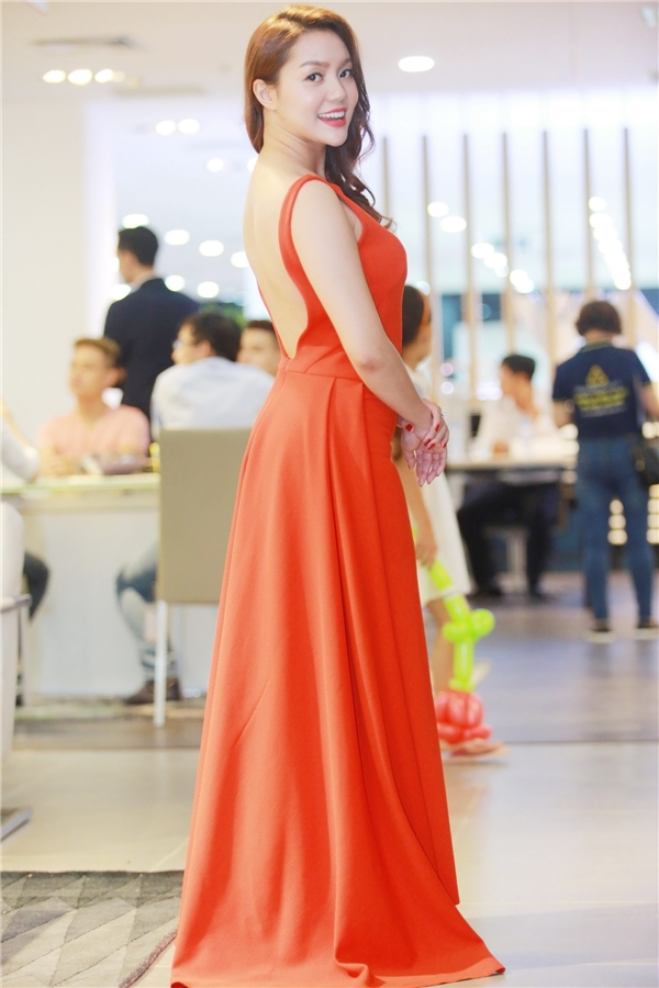 Ca sĩ Ngọc Anh diện đầm xòe điêu đà với tông màu đỏ cam nóng bỏng, bắt mắt.