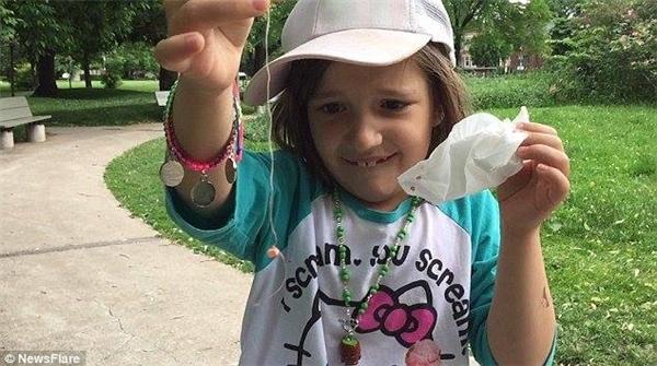 Cô con gái khoe chiến tích là chiếc răng đã được nhổ trong tích tắc. (Ảnh: Internet)