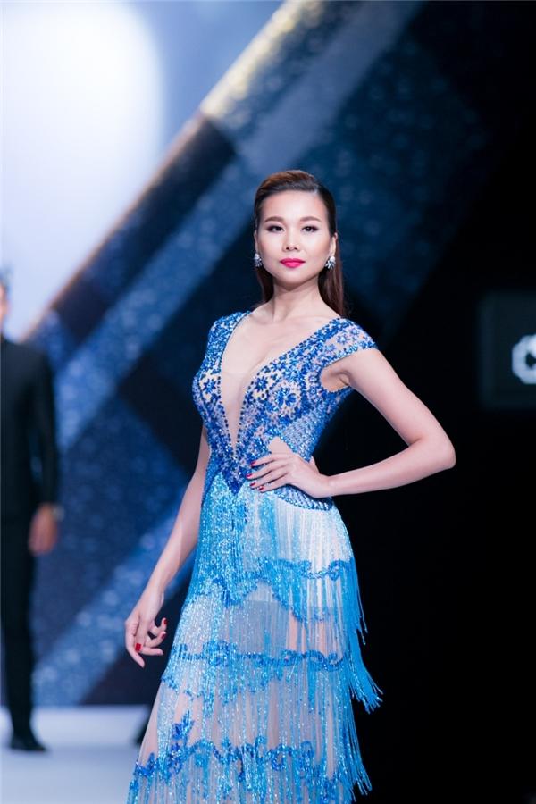 Thanh Hằng diện váy xuyên thấu kết hợp nhiều chi tiết đính kết kì công, tỉ mỉ với hai tông màu vàng, xanh trẻ trung.