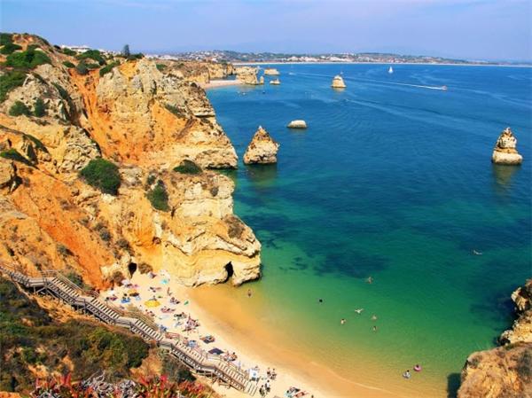 Trong khi đi trên cầu thang để xuống bãi biển Raia do Camilo tại Lagos ở Bồ Đào Nha, bạn có thể chiêm ngưỡng vẻ đẹp của những vách đá và núi bao quanh vịnh. Sau khi thư giãn trên bãi biển yên tĩnh, du khách có thể tới các nhà hàng trên vách đá để thưởng thức những món hải sản tươi ngon. (Ảnh Internet)