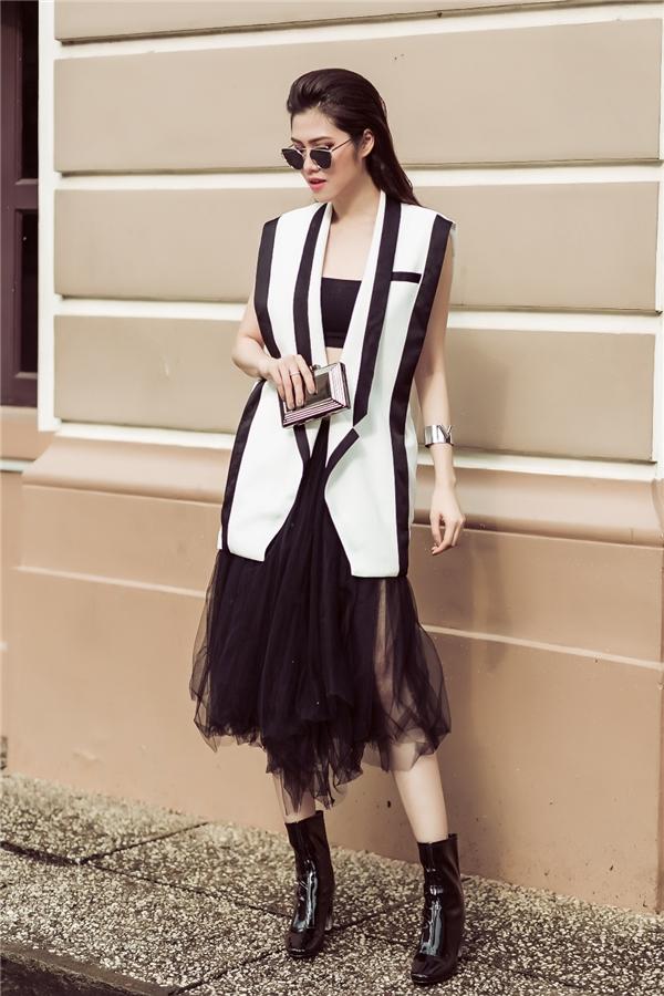 Chọn áo quây sắc đen và chiếc đầm voan phồng cùng màu nhưng Giải vàng Siêu mẫu 2002đã khiến bộ đồ trở nên đẳng cấp và cá tính hơn khi phối với chiếc gilet vest trắng viền đen cách điệu và đôi boot cổ thấp tệp màu.
