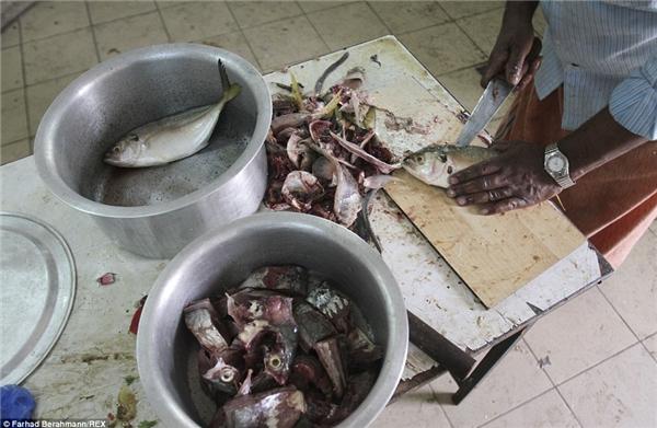 Một người đàn ông đang làm cá với đôi tay trần trong bếp ở Sonapur.(Ảnh:Farhad Berahman)