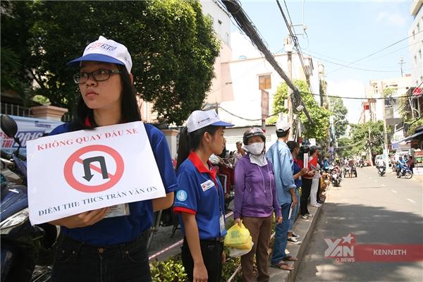Nữ tình nguyện viên này đang hướng dẫn giao thông tạiđiểm thi trường THCS Trần Văn Ơn.