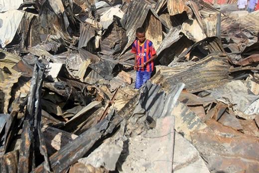 Một cậu bé cố gắng tìm kiếm thứ gì đó có giá trị còn sót lại giữa đống đổ nát sau một đám cháy xảy ra do đánh bom tự sát ở ngoại ô Mogadishu.