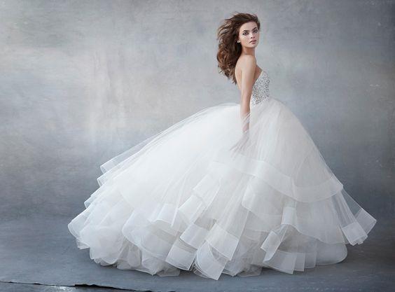 """Có một số nhà thiết kế lại tận dụng độ xòe của váy và tập trung gây ấn tượng từ phần ngực đến thắt eo để các nàng dâu trở nên nhỏ xinh, lộng lẫy nhưng nhẹ mắt hơn thay vìtham lam đắp""""hột"""" ở phần chân váy."""