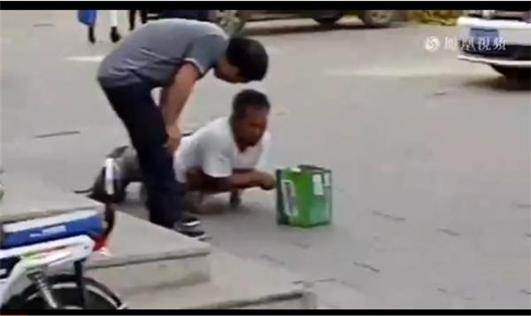 Người đàn ông áo xám hỏi thăm người ăn xin tàn tật khi đang đi ngoài đường. (Ảnh: Cắt clip)