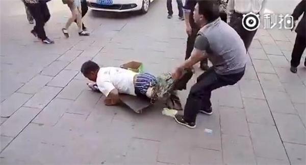 Người đàn ông vội vàng túmgã ăn xin lại khi hắn đang định bỏ đi.(Ảnh: Cắt clip)