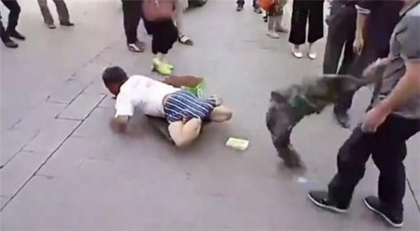 Sau khi chiếc quần bị lột bỏ, nhiều người dân bất ngờ khi thấy hai chân của gã ăn xin hoàn toàn bình thường.(Ảnh: Cắt clip)