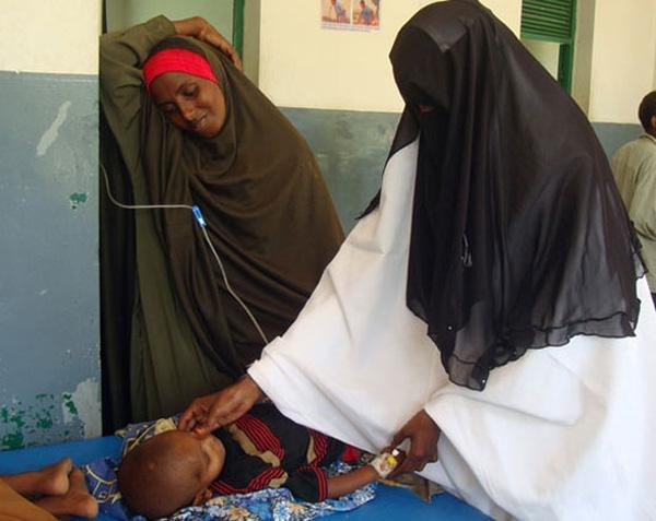 Bác sĩ đang khám cho em bé bị suy dinh dưỡng trong khi mẹ bé đứng nhìn con đầy thương xót.