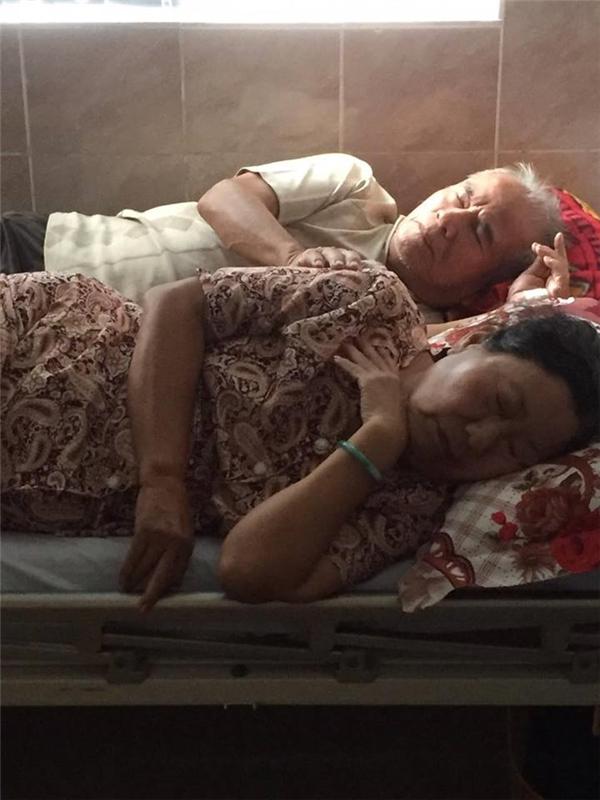 Dù đang ngủ nhưng ông cụ vẫn dò dẫm xoa lưng, bóp tay cho vợ không ngừng.(Ảnh: Như Ý)
