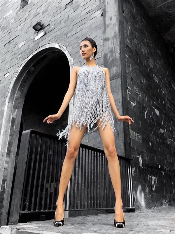 Đôi chân dài thẳng tắp của Lan Khuê được phô diễn khéo léo trong chiếc váy suông màu ánh bạc của Lê Thanh Hòa. Thiết kế được tạo nên bằng kim loại với chi tiết mắc xích độc đáo.