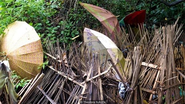 Dân làngdùng một chiếc ô sáng màu để che mưa che nắng cho các thi thể.