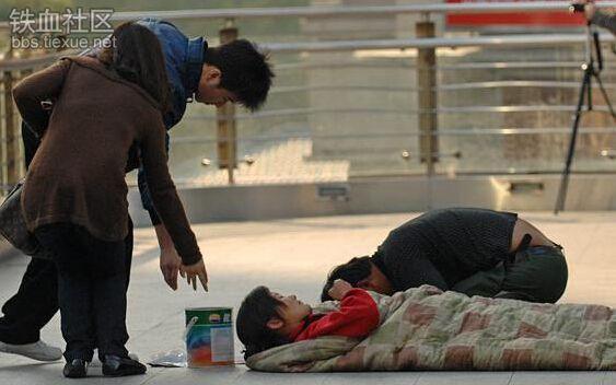 """""""Khấu đầu chắp tay"""" cầu xin người qua lại rủ lòng thương hại bố thí vài đồng cứu vợ chính là """"nhiệm vụ"""" thường ngày của ngườiđàn ông trên. Bức ảnh được chụp lại tại đường phố Thượng Hải, người đàn bà đang nằm chính là vợ anh. Nhiều người bắt gặp liền cảm động và thương hạitrước cảnh ngộ khó khăn của hai vợ chồng. Trên thực tế, cặp đôi này rất khoẻ mạnh, họ liên tục đổi ca cho nhau giả làm người bệnh để xin tiền những người qua lại gần đó."""