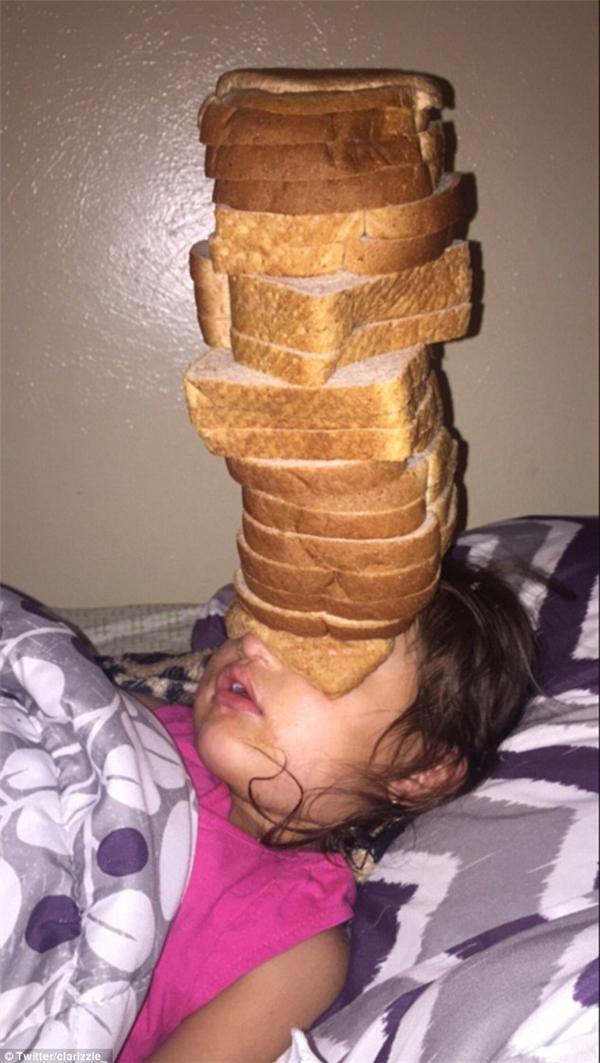 Cô em gái tội nghiệp vẫn say mê ngủ không biết trời đất gì dù trên mặt mình đã có đến... 14 lát bánh mì sandwich. (Ảnh: Clare)