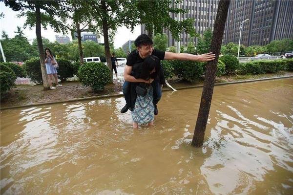 Cô nàng dại trai cõng người yêu qua chỗ nước ngập vì lí do khó đỡ
