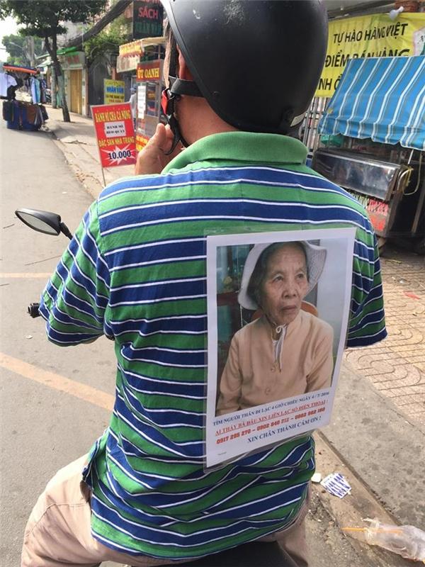 Hình ảnh người đàn ông trung niên dán ảnh bà cụlên người, rong ruổi tìm kiếm khắp các con đường. (Ảnh: NVCC)
