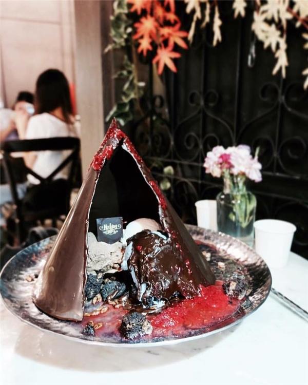 """Sau khi bị ngọn lửa xanh nuốt chửng, """"ngọn núi"""" sẽ lở ra, hé lộ hỗn hợp kem tươi, bánh brownie và sốt raspberry bên trong cực kì hấp dẫn.(Ảnh: Instagram)"""