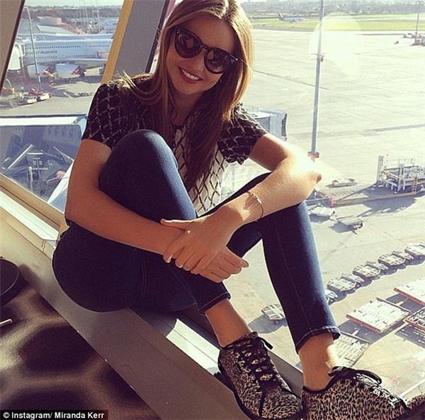 Ngồi tạo dáng tươi vui bên khung cửa sổ kiếng ngập nắng nhìn xuống bãi đậu máy bay như Miranda Kerr ư? (Ảnh: Miranda Kerr)