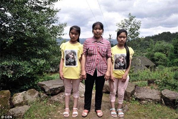 Hai chị em sinh đôi ăn mặc giống hệt nhau bên cạnh mẹ.(Ảnh: CEN)