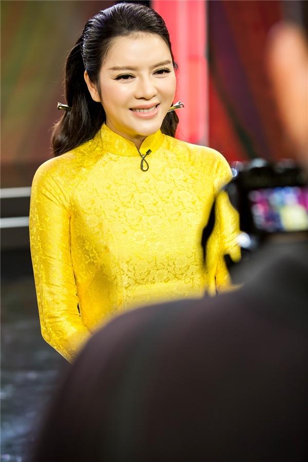 Lý Nhã Kỳ diện áo dài màu vàng rực trên sân khấu.