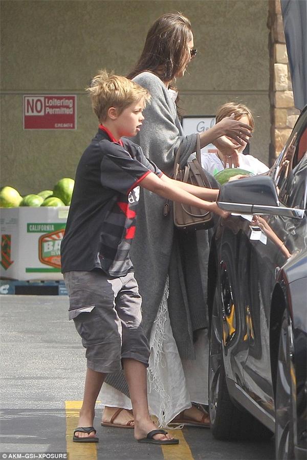 Shiloh phụ giúp mẹ mua sắm và mở cửa ô tô.