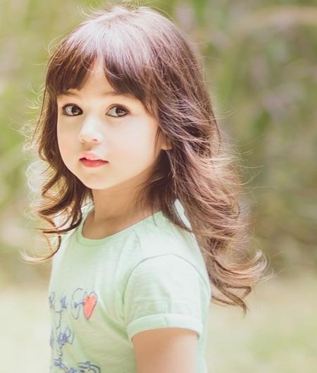 Côbé sở hữu nét đẹp lai hoàn hảo,đôi mắt nâu to tròn, khuôn miệng chúm chím, hai má bầu bĩnh, làn da trắng hồng , cùng nụ cười thiên thần vô cùng đáng yêu.