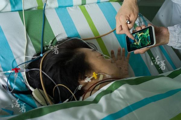 Sau khi sinh, đứa trẻ được đưa đến phòng chăm sóc đặc biệt, chị Hồ Lục nhìn con qua hình ảnh được bác sĩ chụp trên máy điện thoại.