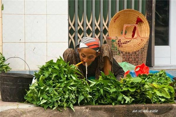 Bữa ăn vội của bà cụ bán rau, ở cái tuổi lẽ ra nên được nghỉ ngơi, cụ vẫn phải tần tảo mưu sinh. (Ảnh: Võ Mậu Khiêm)