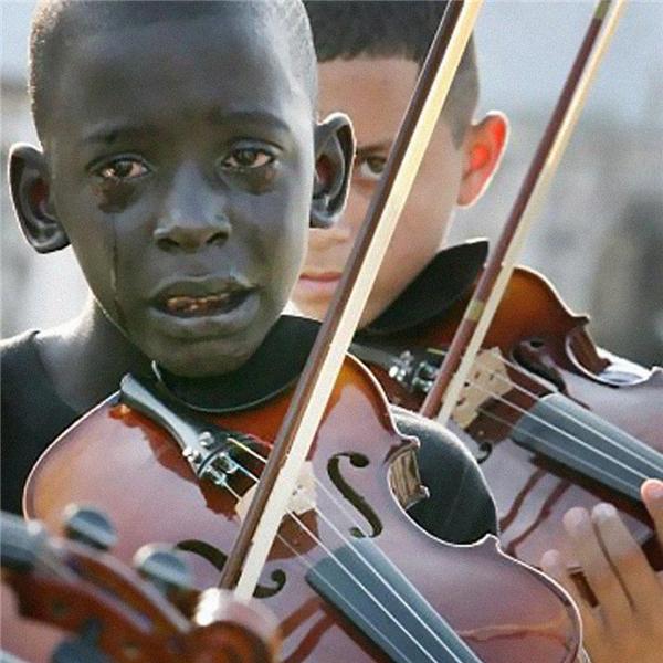 Bức ảnh chụp lại cảnh một cậu bé 12 tuổi người Brazil chơi đàn violon tại lễ tang của thầy mình. Ngày còn sống, thầy cứ như một người bạn quyền lực và thấu hiểu lòng người, ông đã giúp đỡ rất nhiều trẻ em khốn khó thoát cảnh đói nghèo, bạo lực nhờ vào âm nhạc. (Ảnh Internet)