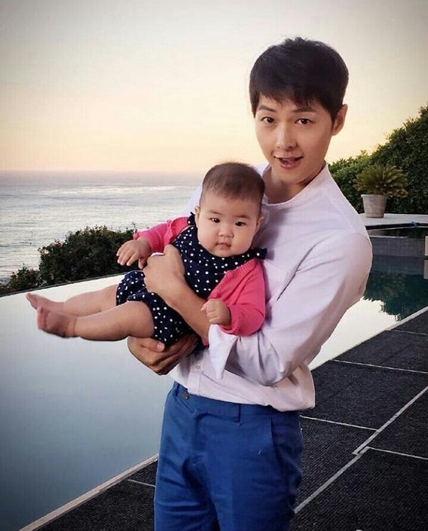 Song Joong Ki bế con gái Chương Tử Di khiến nhiều người càng tin vào việc anh sang Mỹ đóng quảng cáo với nữ diễn viên nổi tiếng Trung Quốc này