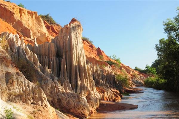Một bên là những núi đá sừng sững màu đất đỏ (Ảnh: Internet)