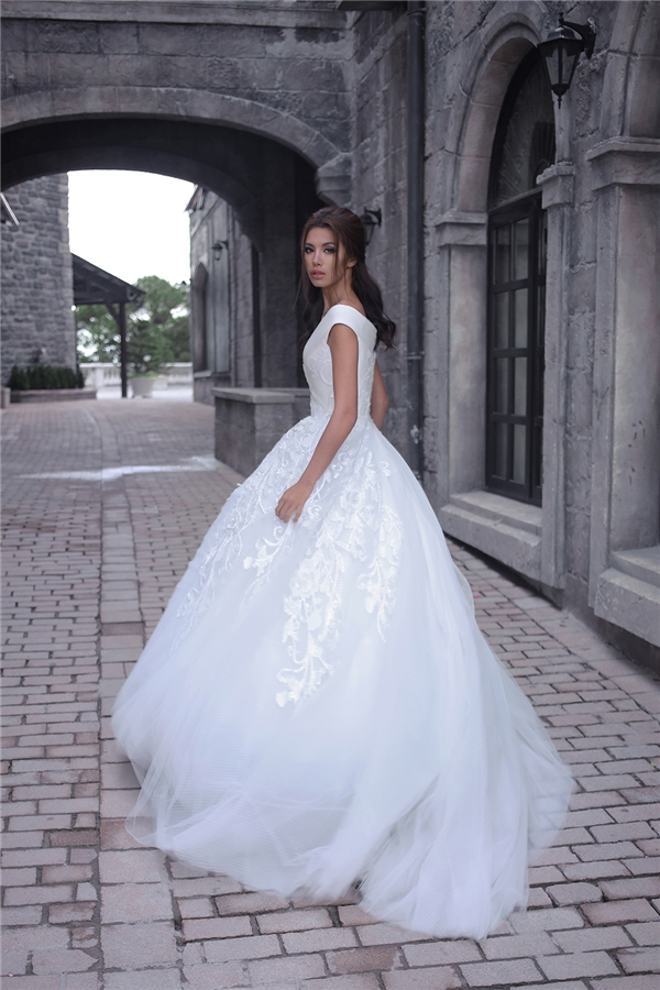 Váy xòe cổ điển được cách điệu ở chi tiết trễ vai hợp xu hướng cùng loạt chi tiết hoa lá đính kết tạo điểm nhấn ở thắt eo.