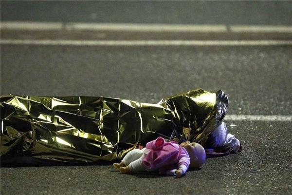 Đây có thể coi là bức ảnh ấn tượng và khắc họa rõ nét nhất tội ác của những kẻ điên cuồng: Một con búp bê nằm trơ trọi bên thi thể một bé gái đã được che lại bằng giấy gói quà. (Ảnh Reuters)