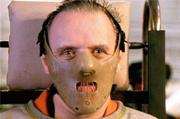 """Hannibal Lecter (Anthony Hopkins) trong The Silence of the Lambs (1991): Đây là nhân vật phản diện hư cấu trong loạt truyện trinh thám kinh dị của Thomas Harris. Bị ám ảnh bởi những lời trăn trối của Vladis Grutas rằng """"Kẻ mạnh sẽ ăn thịt kẻ yếu"""", Hannibal Lecter trở thành kẻ giết người hàng loạt, chuyên ăn thịt người, và sở hữu tâm hồn tăm tối đến rợn người. Trong bộ phim chuyển thể The Silence of the Lambs, hắn là một bác sĩ tâm thần có chuyên môn xuất sắc, nhưng đồng thời là tên sát nhân hàng loạt, tạo ra hàng loạt thảm kịch kinh hoàng. (Ảnh: Orion Pictures)"""