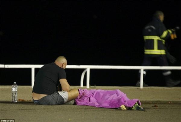 Người đàn ông ngồi thất thần trước thi thể người thân. (Ảnh: Reuters)