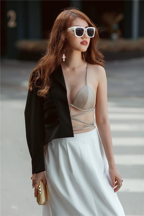 """Jolie Nguyễn """"đốt mắt"""" người đối diện với chiếc áo bra-top mỏng mang diện cùng chân váy và áo khoác blazer bên ngoài. Với những buổi tiệc nhẹ nhàng, bộ cánh này sẽ giúp bạn trở thành tâm điểm mà không cần vẽ vời thêm bất kì điều gì."""