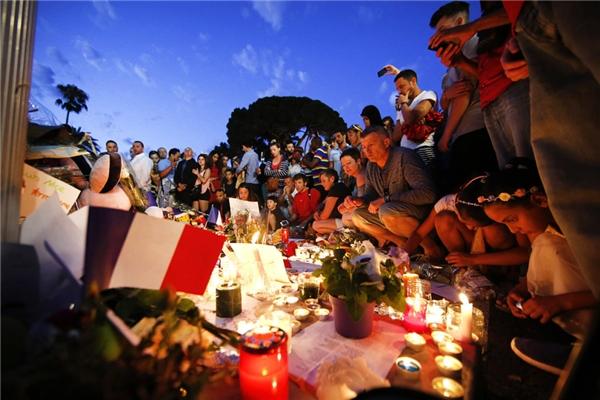 Mọi người tụ tập lại cùng với hoa và nến đế tưởng nhớ các nạn nhân một ngày sau vụ thảm sát ở Pháp. Cụ thể,một chiếc xe tải chạy với tốc độ cao đâm vào đám đông làm thiệt mạng hơn 84 người khi họ đang xem bắn pháo hoa kỉ niệm lễ Quốc khánh tại Nice, trong đó có 10 trẻ em và thanh thiếu niên.(Ảnh:Eric Gaillard )